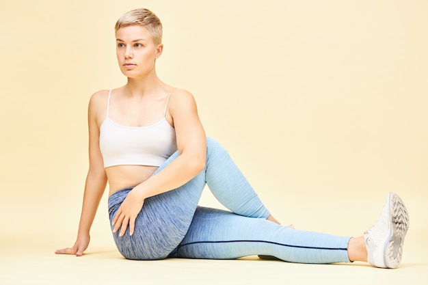 Jeune femme en forme sportive pratiquant le yoga, faisant une variation de la pose d'ardha matsyendrasana ou half lord qui dynamise la colonne vertébrale et stimule la digestion, assis sur le sol avec un genou plié, tordant