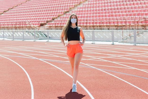Jeune femme en forme en tenue de sport et masque de protection contre le coronavirus sur piste rouge et terrain de volley-ball pendant l'entraînement en plein air au stade
