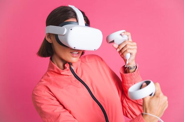 Jeune femme en forme en veste de sport et lunettes de réalité virtuelle jouant à des jeux de combat de boxe sur rose