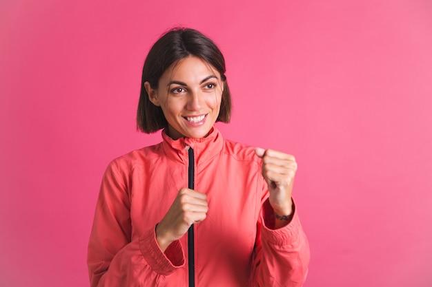 Une jeune femme en forme de veste de sport sur rose combat le geste de la boîte
