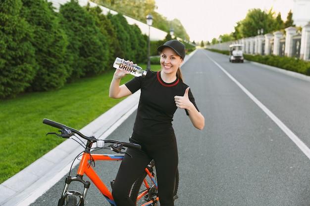 Jeune femme forte athlétique souriante en uniforme noir, casquette tenant pointant sur une bouteille d'eau, route à vélo à l'extérieur par une journée ensoleillée de printemps ou d'été. remise en forme, sport, concept de mode de vie sain.