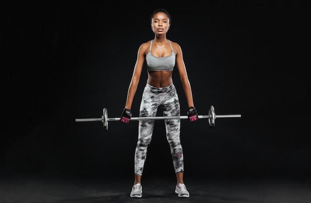 Jeune femme forte avec un beau corps athlétique faisant des exercices avec des haltères isolés sur un mur noir
