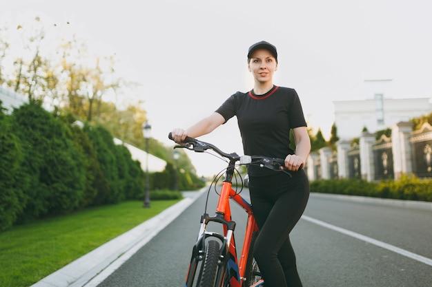 Jeune femme forte brune athlétique en uniforme noir, cap stop riding road sur vélo noir avec des éléments orange à l'extérieur le jour ensoleillé de printemps ou d'été. remise en forme, sport, concept de mode de vie sain.