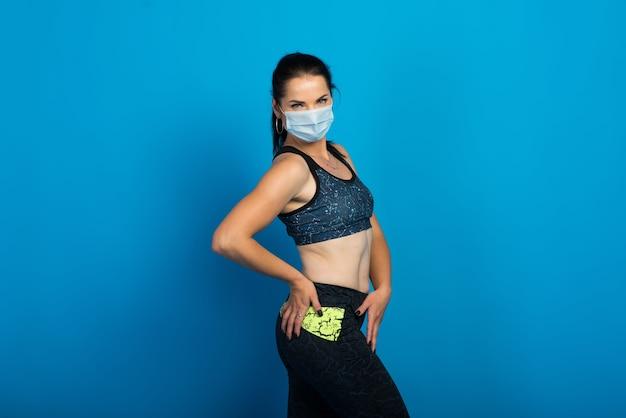 Jeune femme forte de remise en forme dans un masque facial travaillant isolé