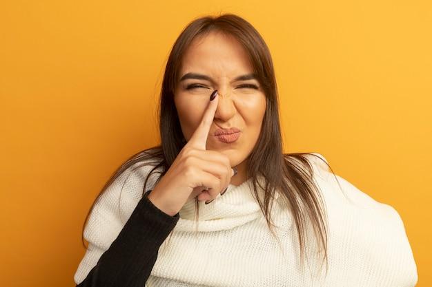 Jeune femme avec un foulard blanc à la confusion pointant avec l'index sur son nez