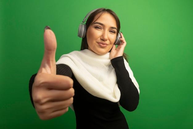 Jeune femme avec foulard blanc et écouteurs souriant joyeusement montrant les pouces vers le haut
