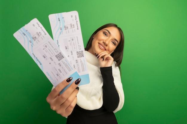 Jeune femme avec foulard blanc montrant les billets d'avion avec sourire sur le visage heureux et positif