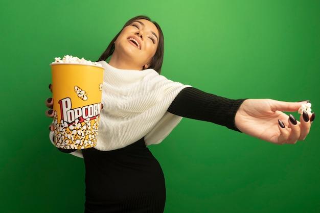 Jeune femme avec foulard blanc montrant seau avec pop-corn heureux et positif souriant gaiement avec le bras