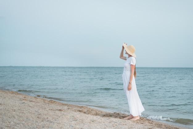 Jeune femme fragile en longue robe blanche debout au bord de l'eau sur la mer