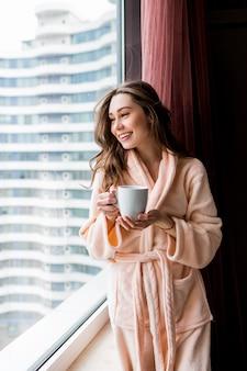 Jeune femme fraîche en peignoir rose tendre boire du thé, regardant par la fenêtre.