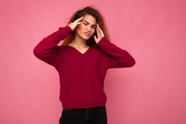 Jeune femme frisée brune attirante émotionnelle avec des émotions sincères portant un pull rose à la mode