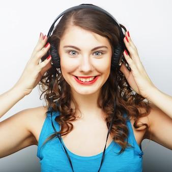 Jeune femme frisée avec un casque d'écoute de musique.