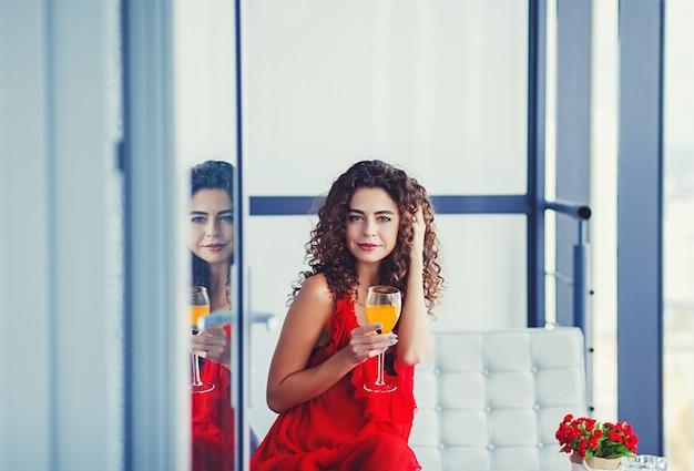 Jeune femme frisée dégustation de jus de fruits