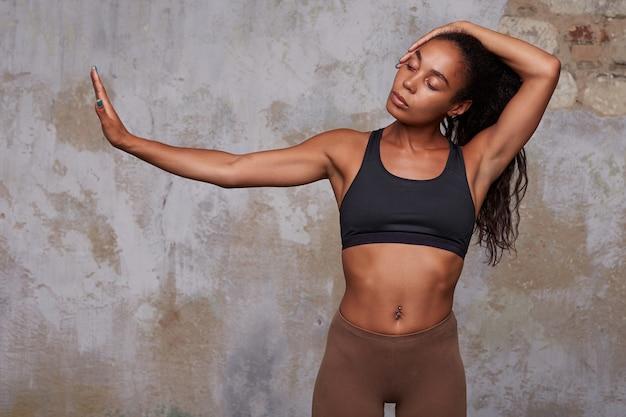 Jeune femme frisée mince aux cheveux noirs avec piercing au nombril faisant élément de danse avec les mains levées, regardant calmement de côté tout en posant sur le mur de briques