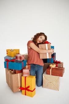 Jeune femme frisée parmi les coffrets cadeaux sur blanc