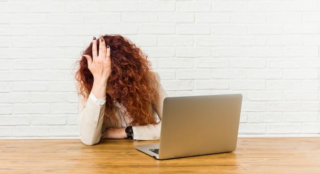 Jeune femme frisée rousse travaillant avec son ordinateur portable en oubliant quelque chose