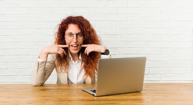 Jeune femme frisée rousse travaillant avec son ordinateur portable sourit, pointant ses doigts vers la bouche.