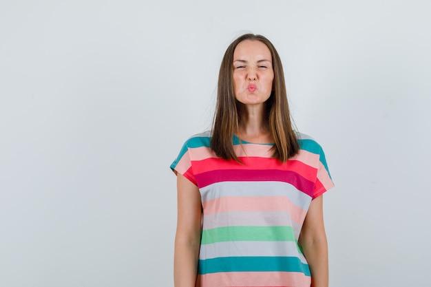 Jeune femme fronçant le visage et les lèvres boudeuses en t-shirt, vue de face.