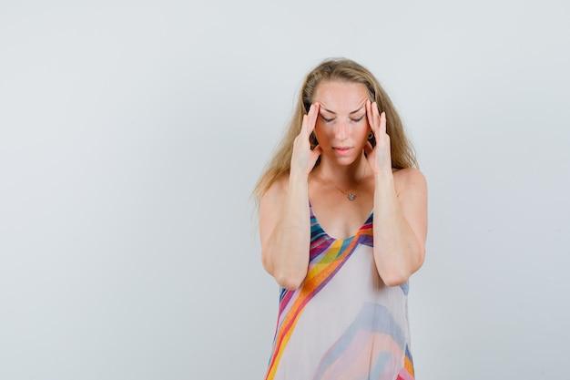 Jeune femme frottant ses tempes en robe d'été et l'air fatigué.