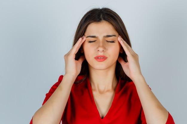 Jeune femme frottant les tempes en chemisier rouge et à la fatigue