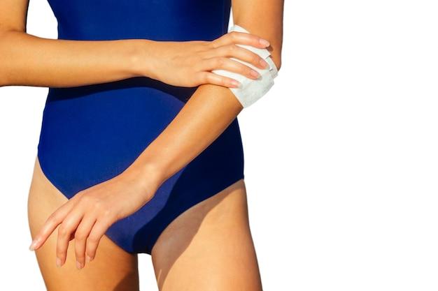 La jeune femme frotte une serviette humide sur la peau des mains sur l'isolat de plage
