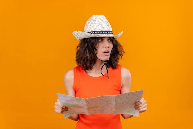 Une jeune femme frustrée aux cheveux courts dans une chemise orange portant un chapeau de soleil tenant la carte et à côté