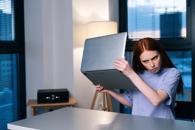 Jeune femme frustrée confuse par un problème d'ordinateur portable assis au bureau dans le bureau à domicile près de la fenêtre le soir à la fin.