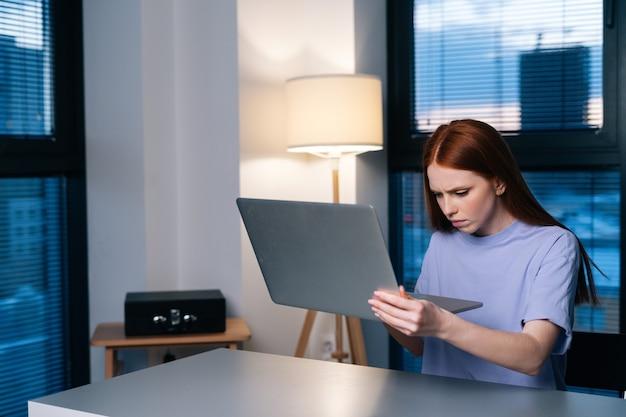 Jeune femme frustrée confuse par un problème d'ordinateur portable assis au bureau dans le bureau à domicile