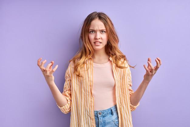 Jeune femme frustrée et irritée se répandant les mains avec choc et incompréhension, que voulez-vous faire un geste.