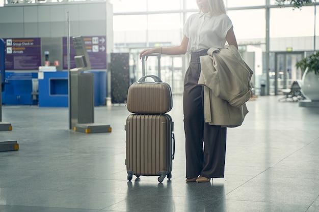 Jeune femme frustrée mettant sa main sur la valise en attendant son collègue