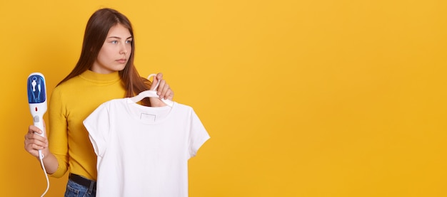 Jeune femme fumant ses vêtements à la maison, tenant un fer à vapeur et un t-shirt blanc sur des cintres dans les mains, regardant de côté avec un regard sérieux, posant contre le mur jaune.