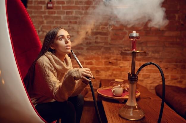 Jeune femme fume le narguilé au bar, se détendre