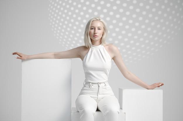 Jeune femme futuriste assise sur cube
