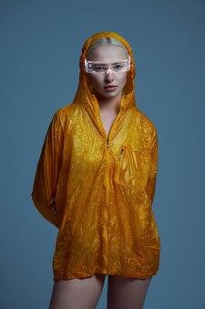 Jeune femme futuriste en imperméable et lunettes modernes, fond gris. femme sexy dans un style de réalité virtuelle, technologie future, concept de futurisme