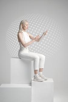 Jeune femme futuriste en vêtements blancs assis sur un cube, fond gris clair. personne de sexe féminin dans un style de réalité virtuelle, technologie future, concept de futurisme