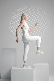 Jeune femme futuriste en vêtements blancs se dresse sur cube, fond clair. personne de sexe féminin dans un style de réalité virtuelle, technologie future, concept de futurisme, thème cyber ou robot