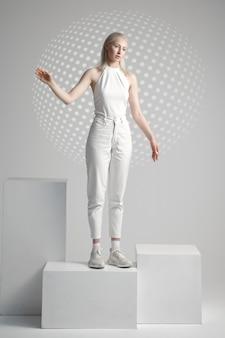 Jeune femme futuriste en vêtements blancs se dresse sur un cube, fond gris clair. personne de sexe féminin dans un style de réalité virtuelle, technologie future, concept de futurisme, thème cyber ou robot