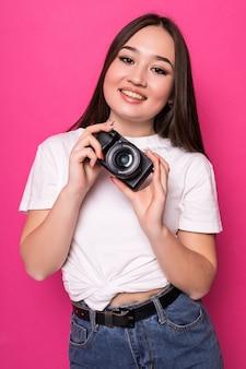 Jeune femme gaie avec appareil photo sur mur rose
