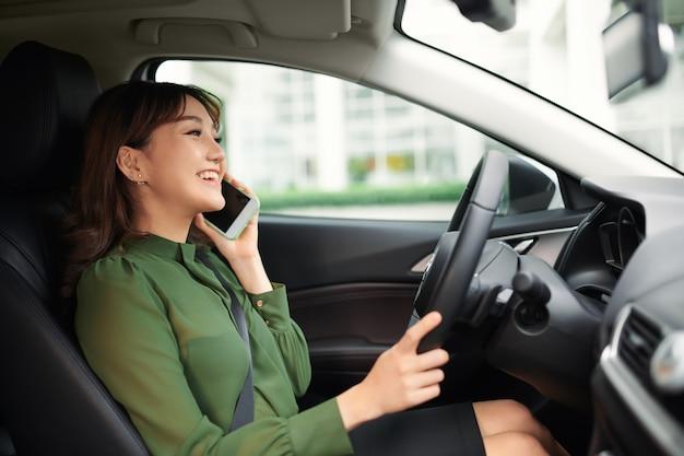 Jeune femme gaie conduisant une voiture et parlant sur le smartphone