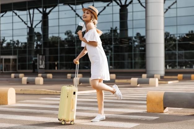 La jeune femme gaie dans la robe blanche élégante et le canotier tient la valise et le passeport jaunes