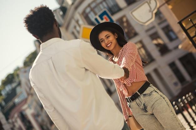 Jeune femme gaie dans des vêtements d'été élégants tirant doucement la main de son petit ami et souriant tout en marchant avec lui
