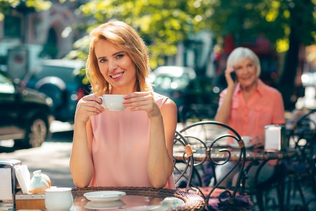 Jeune femme gaie à la table de café de rue s'asseyant avec une tasse de café et souriant