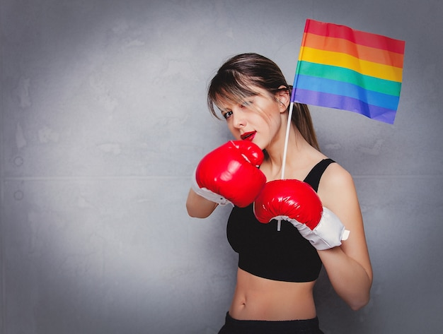 Jeune femme en gants de boxe avec drapeau lgbt
