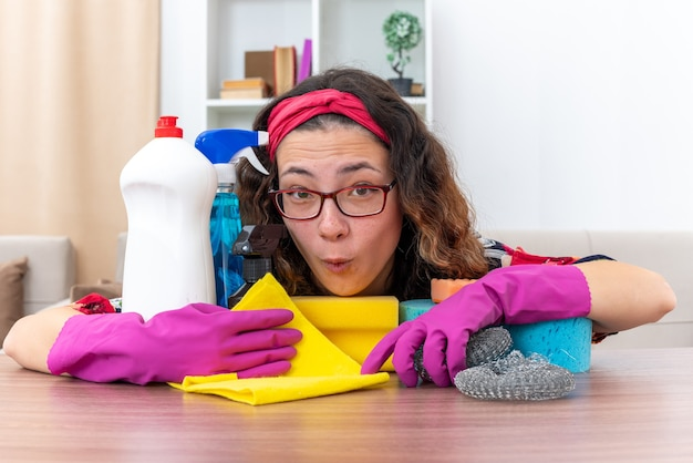 Jeune femme en gants de caoutchouc étonnée et surprise assise à la table avec des produits de nettoyage et des outils dans un salon lumineux