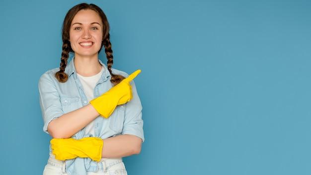 Jeune femme en gants pour le nettoyage sur un fond bleu isolé