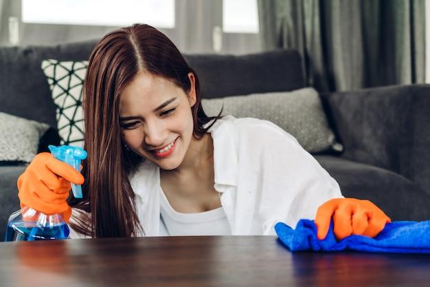 Jeune femme en gants de protection à l'aide d'un vaporisateur et d'un chiffon lors du nettoyage de la maison dans le salon à la maison. travaux ménagers et concept de nettoyage à domicile