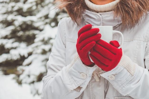 Jeune femme en gants rouges tient la tasse de thé dans ses mains
