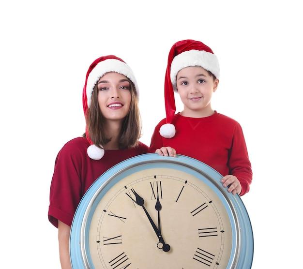 Jeune femme et garçon mignon en bonnets de noel avec horloge. notion de compte à rebours de noël