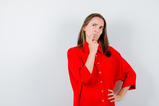 Jeune femme gardant le doigt sur le bord des lèvres, levant les yeux en blouse rouge et l'air pensif, vue de face.