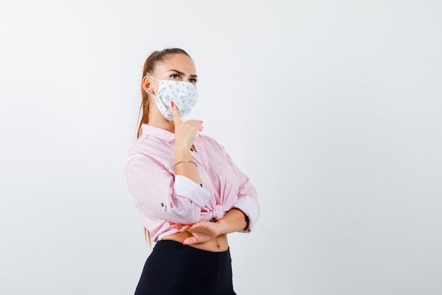 Jeune femme gardant le doigt sur la joue en chemise, pantalon, masque et regardant pensif, vue de face.